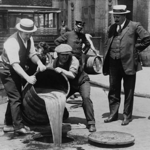 New York City Deputy Police Commissioner John A. Leach watches agents pour liquor into sewer following a raid during prohibition (c1921).