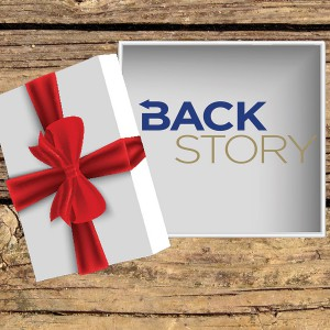 Modified stock images showing an open gift box containing the BackStory logo on a wooden table.