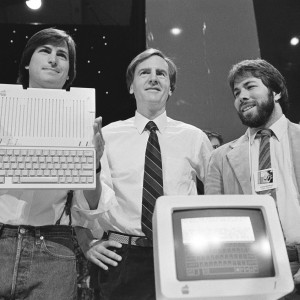 In this April 24, 1984 file photo, Steve Jobs, left, chairman of Apple Computers, John Sculley, center, president and CEO, and Steve Wozniak, co-founder of Apple, unveil the new Apple IIc computer in San Francisco, Calif. Apple has become the world's first company to be valued at $1 trillion, the financial fruit of tasteful technology that has redefined society since two mavericks named Steve started the company 42 years ago. Source: AP Images