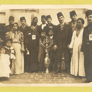 A group of immigrants, most wearing fezzes, surrounding a large vessel which is decorated with the star and crescent symbol of the Moslem religion and the Ottoman Turks. Circa 1902-1913. Source: NYPL Digital Collections