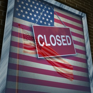 Closed United States of America concept as a metaphor for US government shutdown or failed American business and strict immigration policy as a store window sign with a reflection of a flag on the glass. Source: Adobe Stock