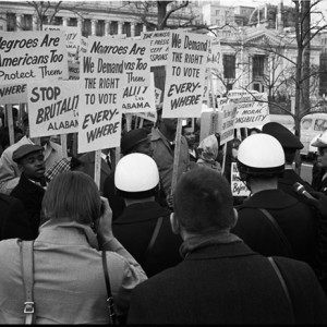 """African American demonstrators outside the White House, with signs """"We demand the right to vote, everywhere"""" and signs protesting police brutality against civil rights demonstrators in Selma, Alabama. March 12, 1965. Source: Library of Congress"""