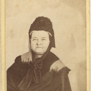 """""""Mary Todd Lincoln with Abraham Lincoln's 'spirit.'"""" Mary Todd Lincoln, seated, head and torso, hands in lap, wearing mourning gown and bonnet, with spirit figure of Lincoln behind her resting his hands on her shoulders by William H. Mumler circa 1872. Source:  Lincoln Financial Foundation Collection, Allen County Public Library, Fort Wayne, Indiana"""