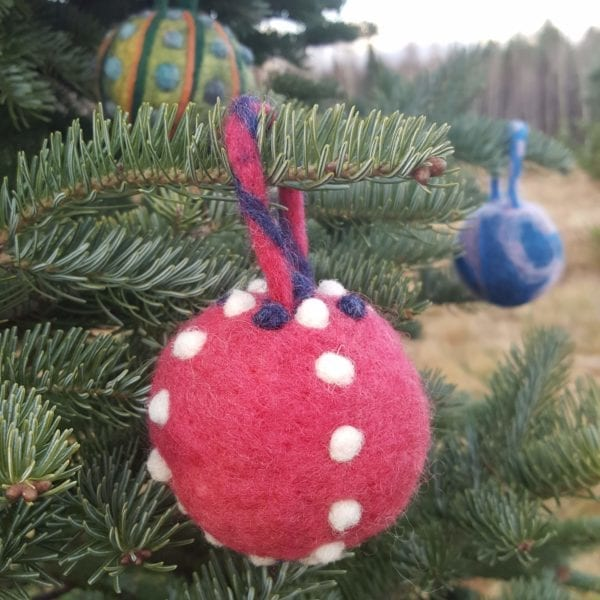 Hand felted Christmas Tree Ball Ornaments by Hillary Dow, Made in Maine, pictured in a tree farm