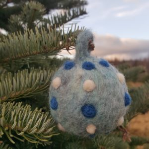 Hand felted Blue Christmas Tree Ball Ornaments by Hillary Dow, Made in Maine, pictured in a tree farm