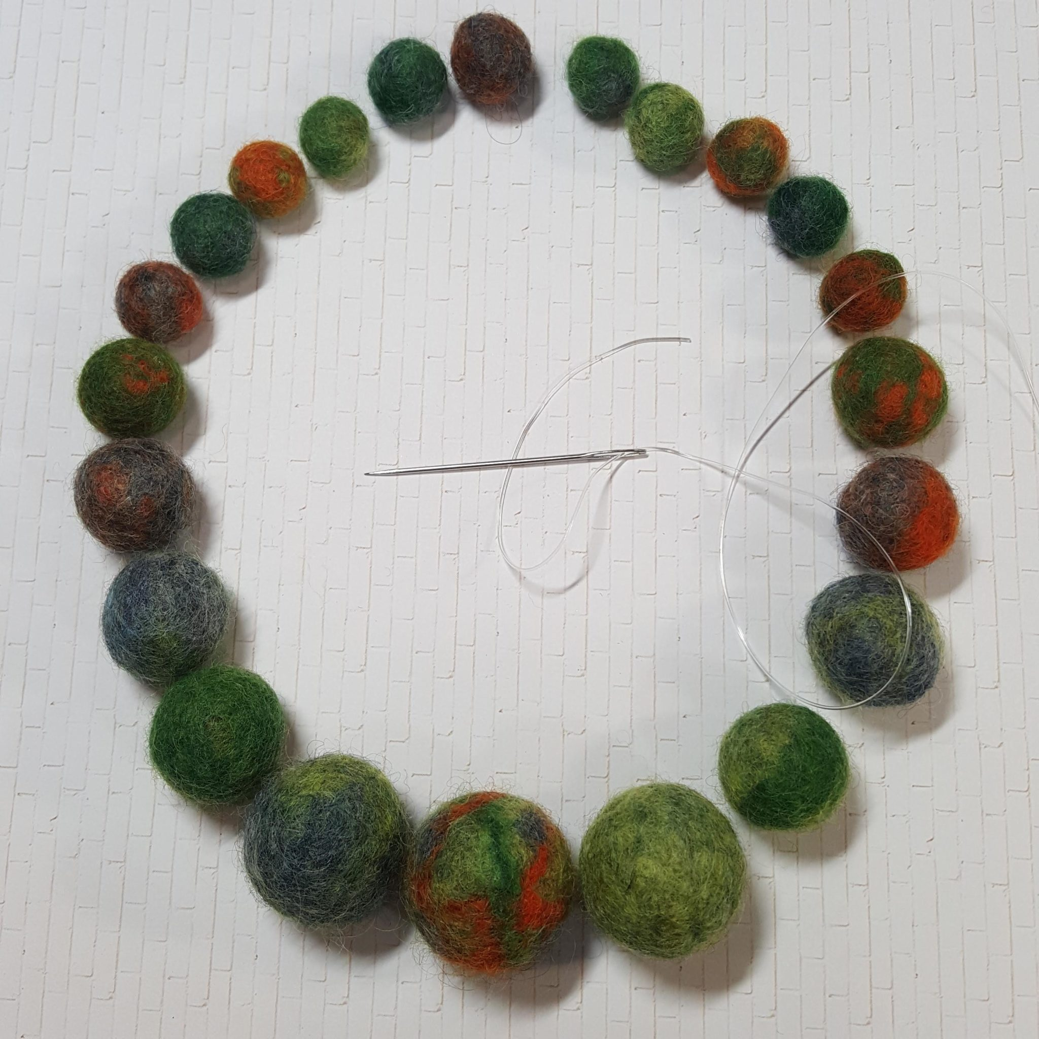 stringing a wool bead necklace