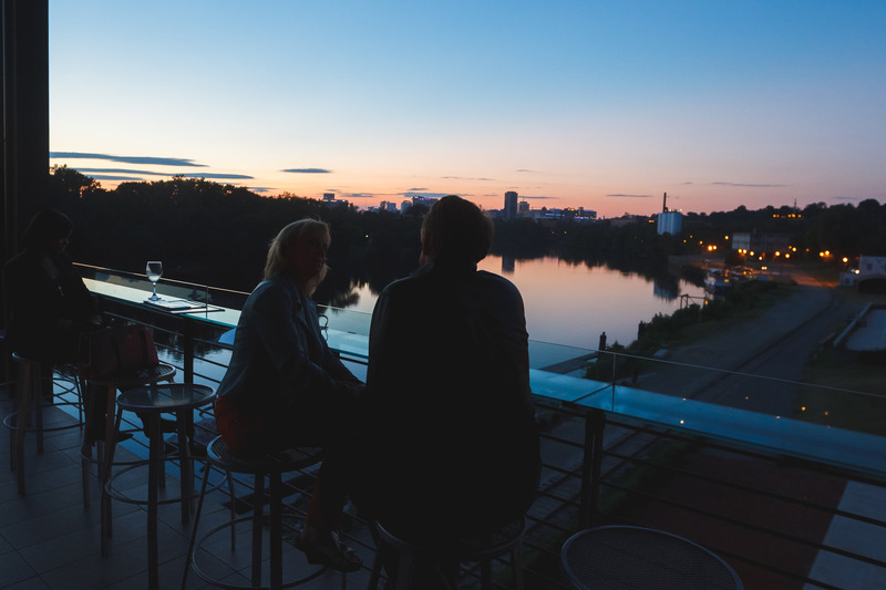 Two patrons watching the sunset on the deck at the Boathouse in Richmond, VA