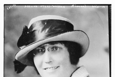 Black and white photo portrait of a woman wearing un-rimmed glasses and a short brimmed hat with a satin bow on it.