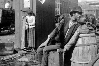 A Brooklyn Longshoreman sitting on a barrel by the street. There's are horses and carriages going down what is presumably Broadway St.