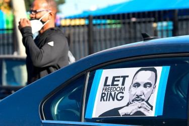 """A car window with a sign in it that reads """"let freedom ring"""" with an illustration of Martin Luther King, Jr."""