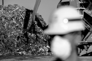 A pile of trash at a landfill behind a member of the Army Corps of Engineers.