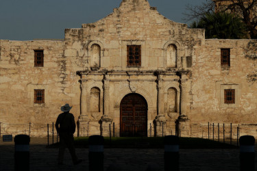 A  man standing in front of the Alamo Complex in San Antonio.