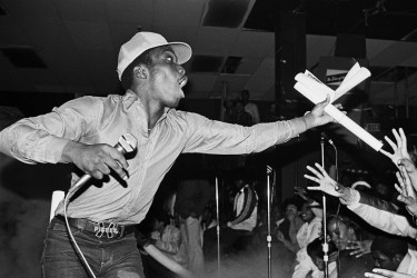 Almighty Kay Gee, of the Cold Crush Brothers, throwing out posters of the group at Harlem World, circa 1981.