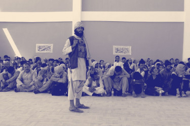 Taliban soldier in front of a large group of Afghan people.