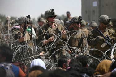 US soldiers stand guard behind barbed wire as Afghans sit on a roadside near the military part of the airport in Kabul on August 20, 2021.