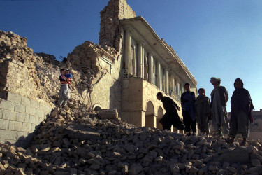 Afghan children standing in rubble