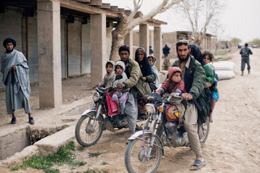 Residents of Marja returning to their village on motorcycles