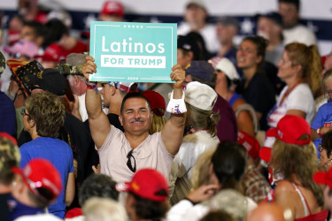 "Man at Trump rally holding a ""Latinos for Trump"" sign."
