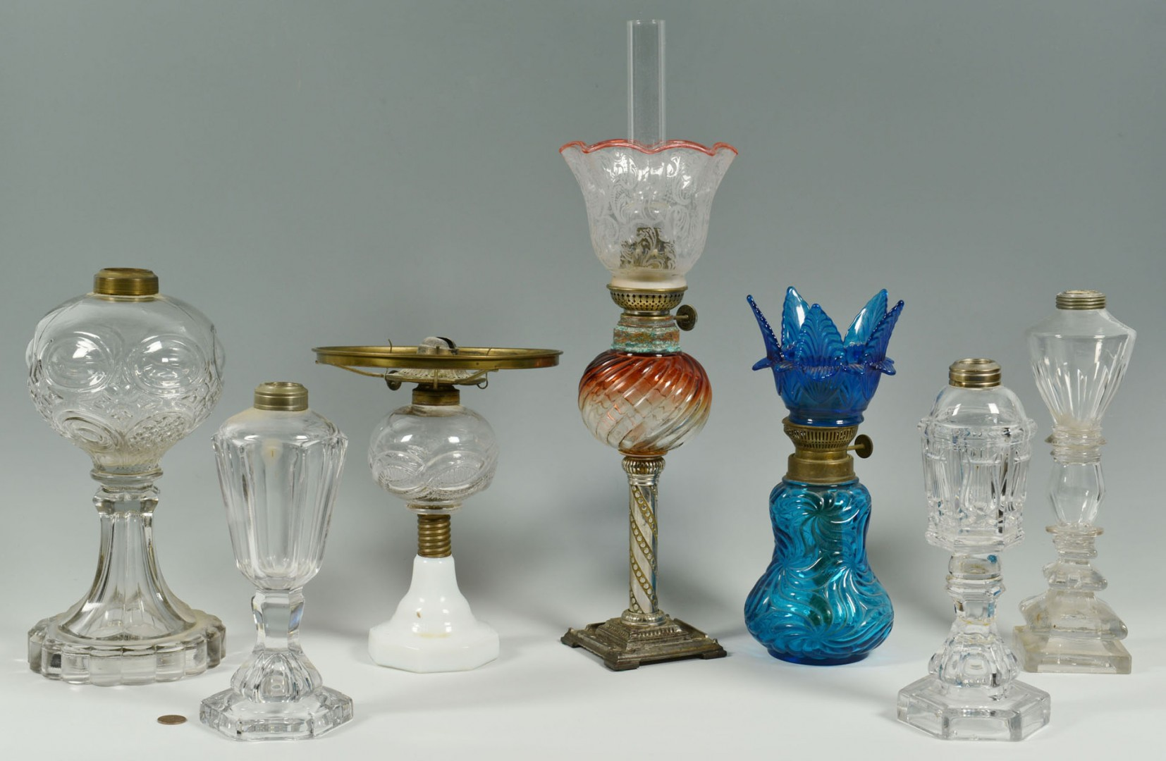 Lot 284: Grouping of colored and colorless oil lamps, 7 tot