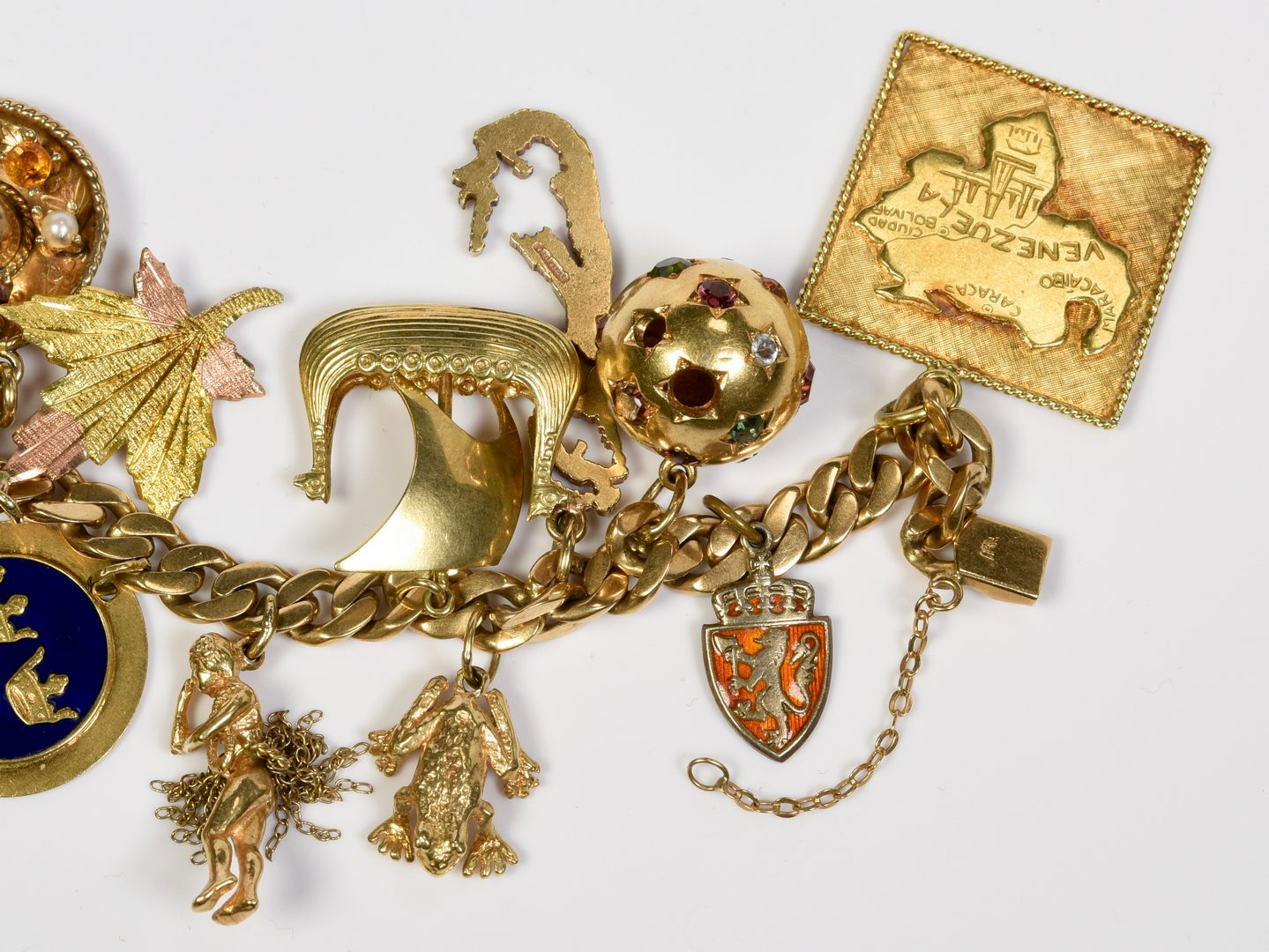 Lot 408: 14K Charm Bracelet, 88.2 grams, 16 charms