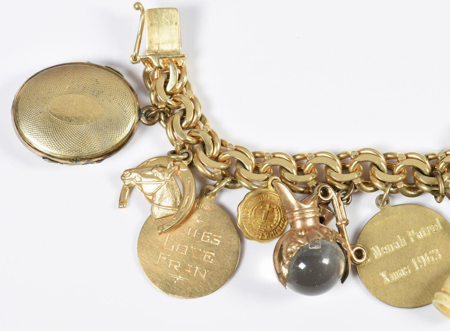 Lot 781: 14K Charm Bracelet, drum, heart, horseshoe, etc.