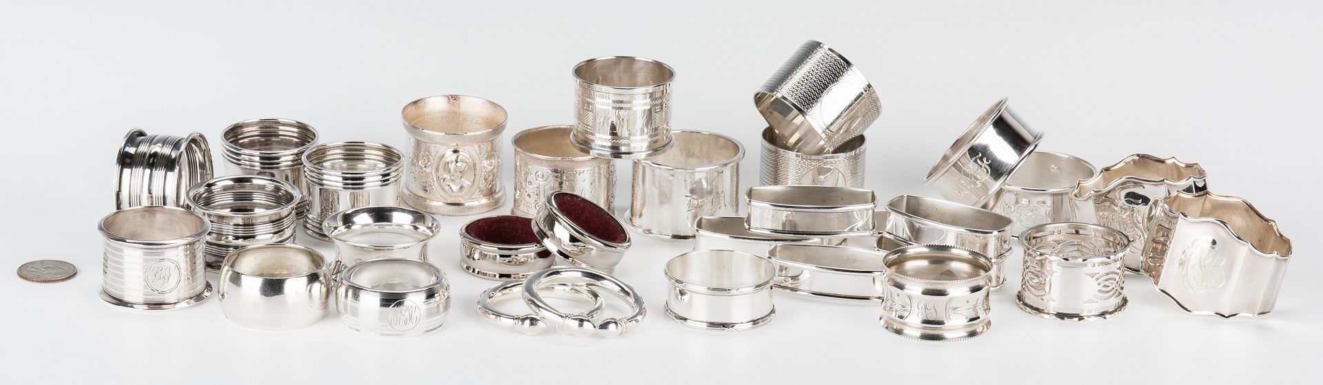 Lot 854: Assembled Group 31 Napkin Rings, most Sterling