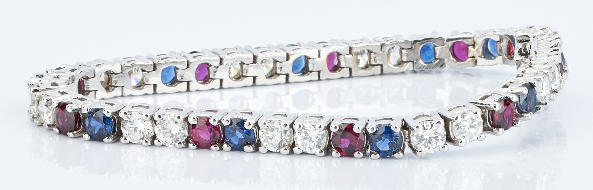 Lot 39: Diamond, Ruby, and Sapphire Tennis Bracelet