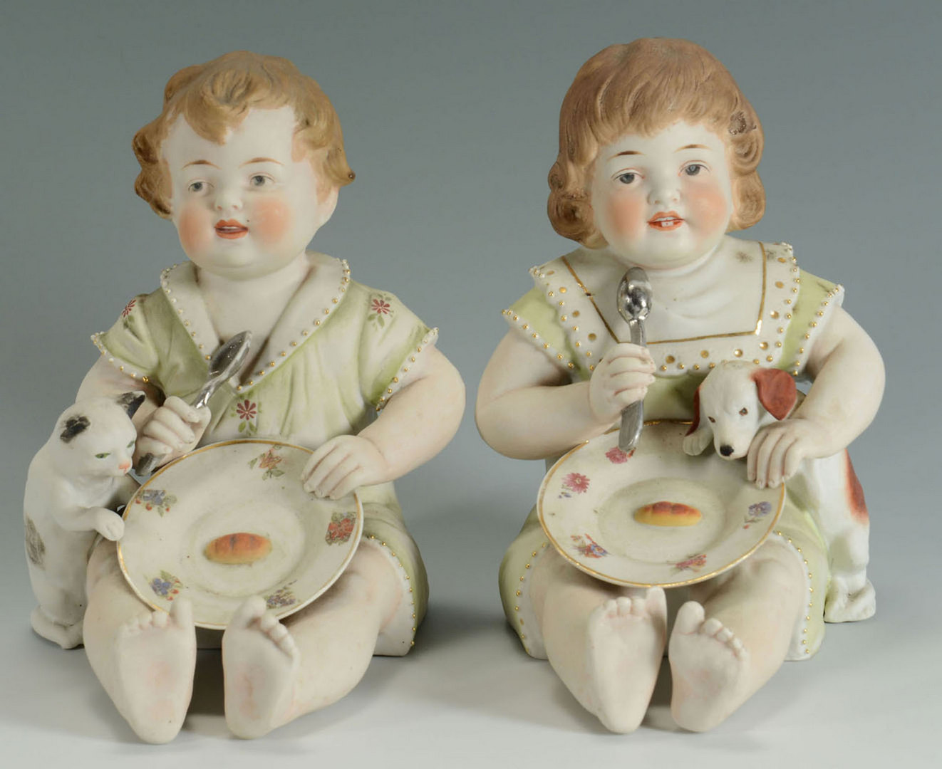 Lot 561: Pair of Large Bisque Piano Babies with dog and cat