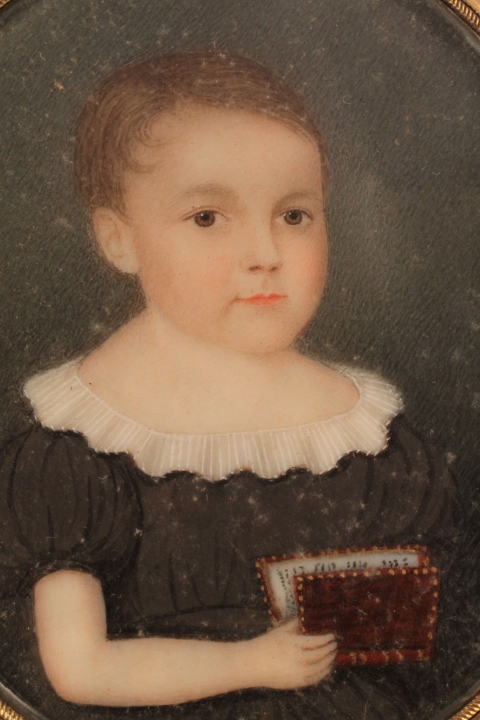 Lot 139: Portrait miniature of child with book, American School