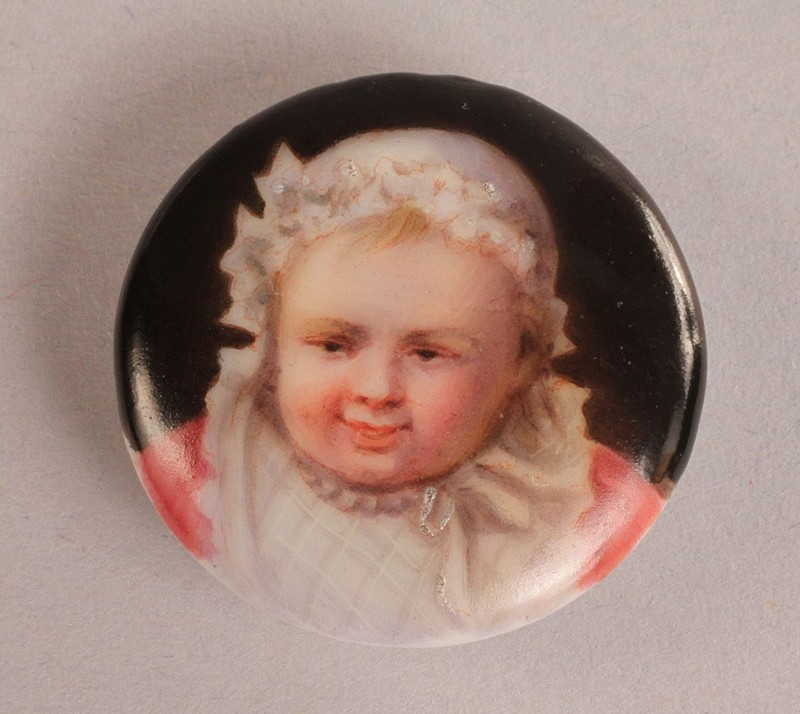 Lot 314: Pair of enamel buttons depicting children