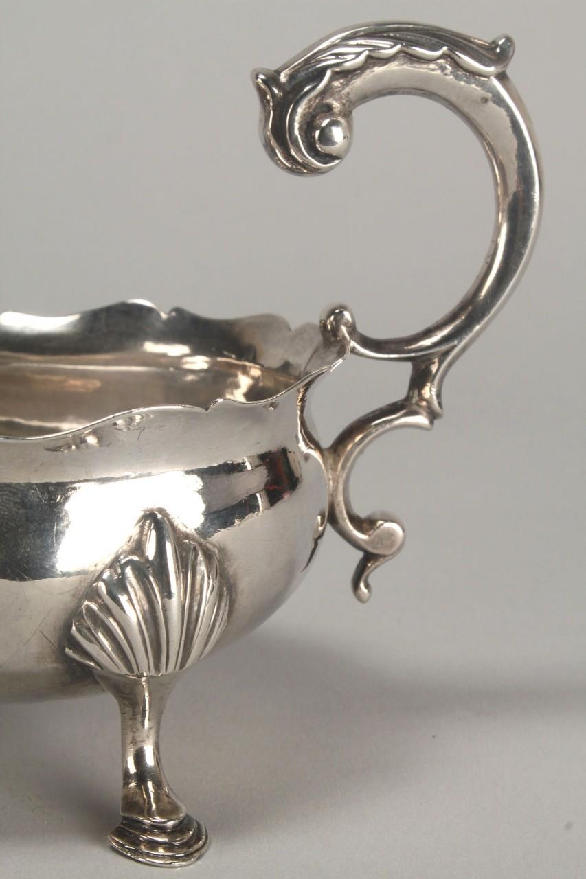 Lot 152: George III Rococo silver sauce boat or cream jug
