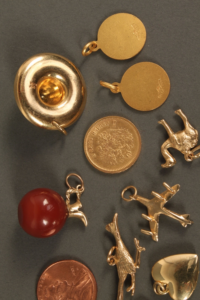 Lot 395: Eleven 18K & 14K charms plus 1 coin