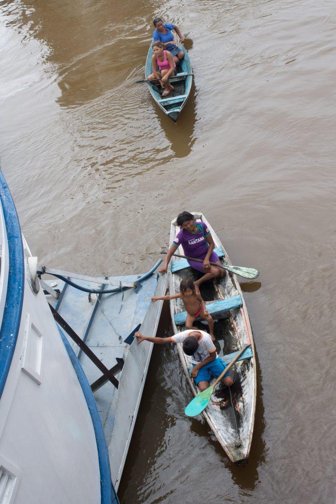 Além do pessoal que espera sacos com roupas e alimentos, vez ou outra, entram vendedores no barco: na foto, eles vinham com camarões secos. Crédito: Renata Helena Rodrigues