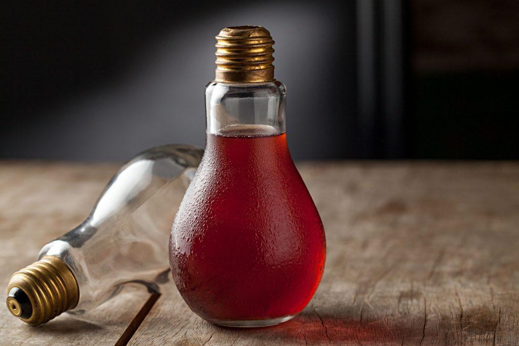 O Âmbar vem numa taça em formato de lâmpada e combina cachaça, Campari e licor de cereja. Foto: Rodrigo Azevedo