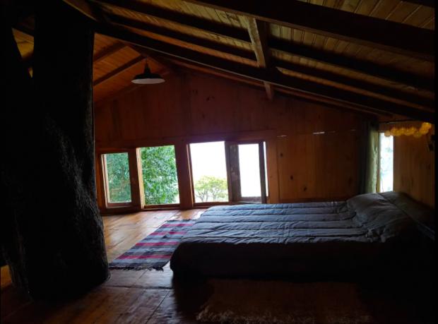 No andar de cima da casa na árvore, o quarto tem vista para as montanhas.