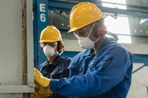 Two Blue Collar Workers Wearing Protective Equipment