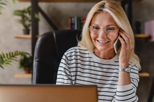 Smiling Casual Senior Woman Using Laptop While Talking On Smartphone.