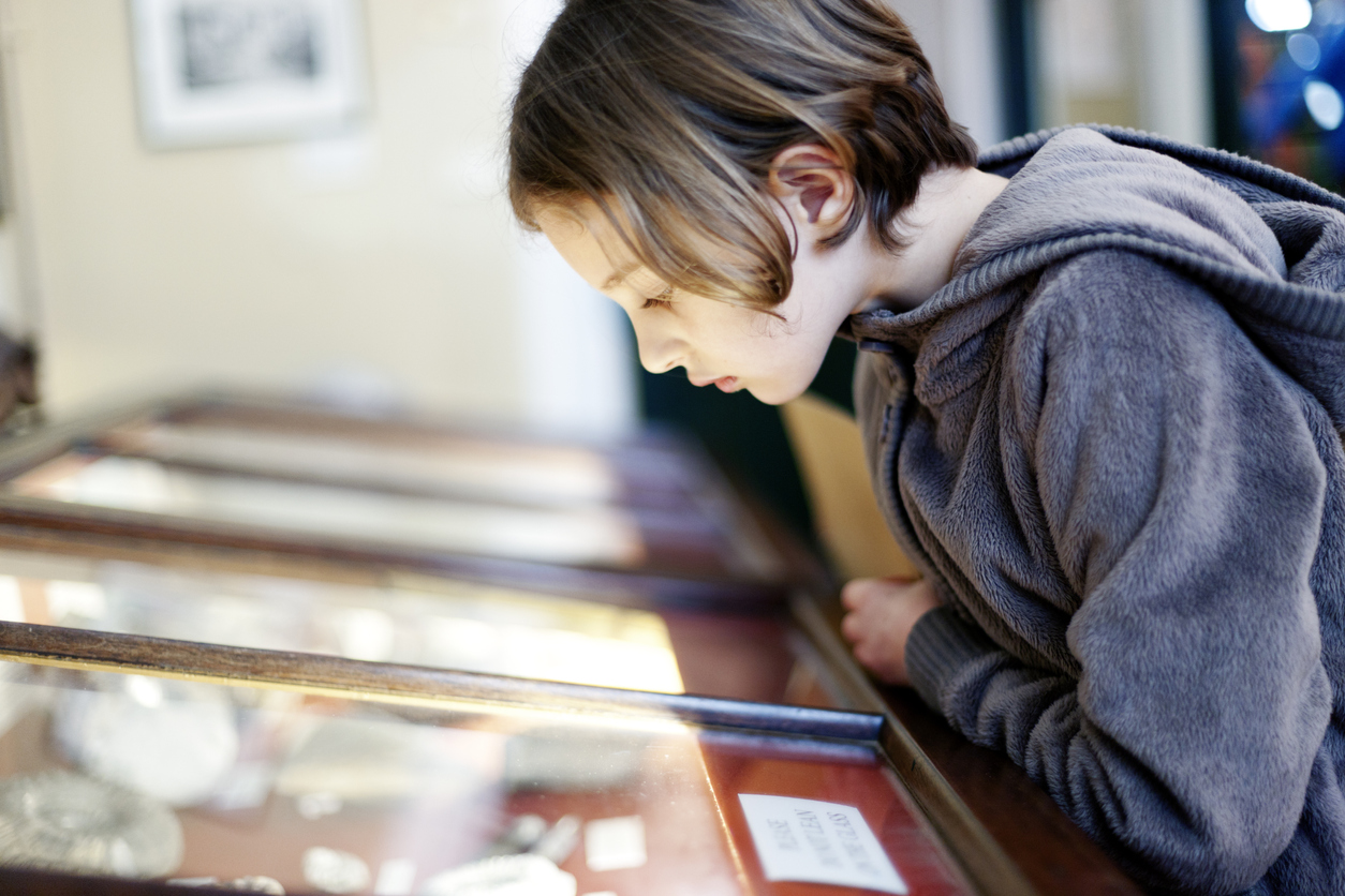 A young girl looking at an exhibit in a glass display case in a museum