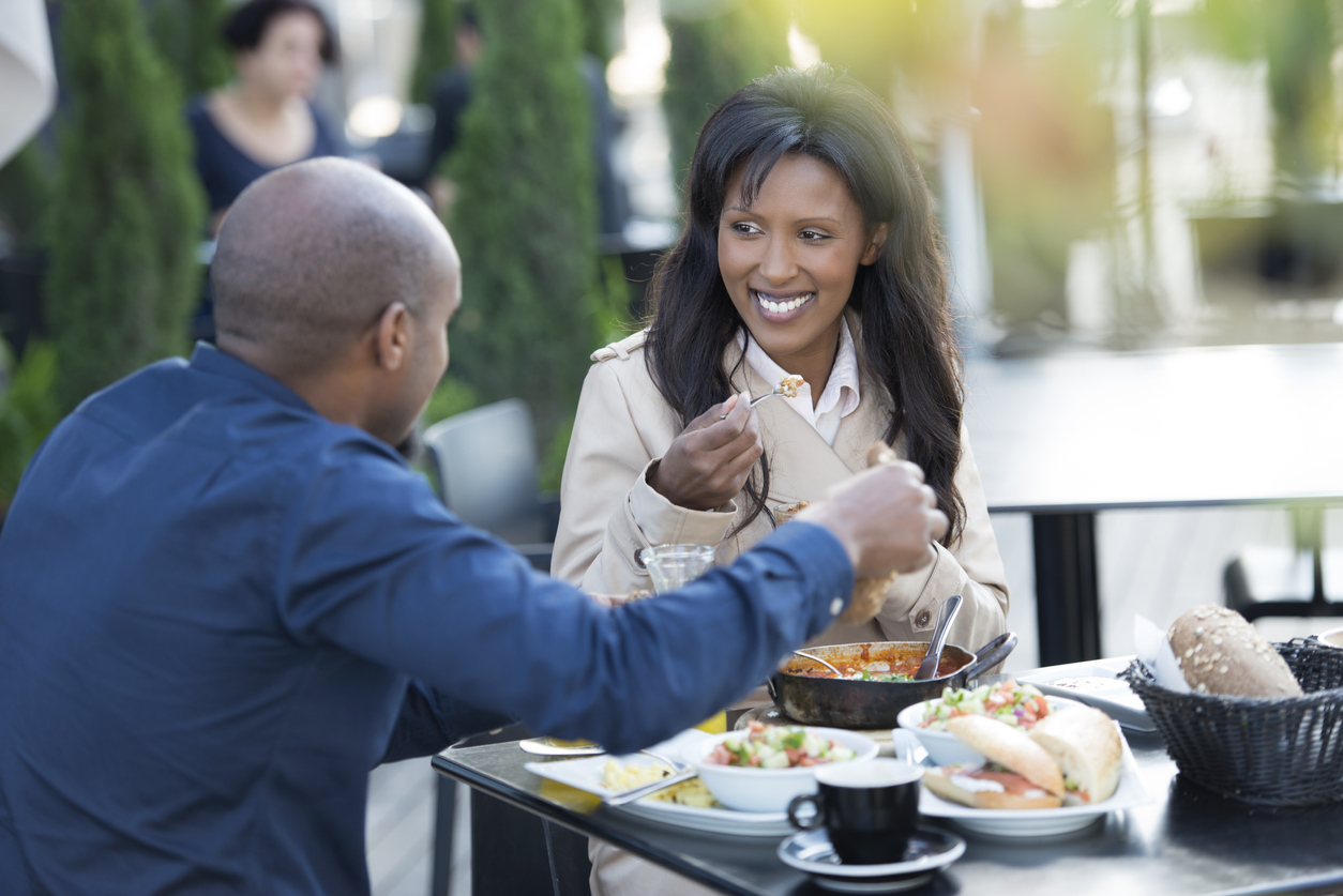 Couple eating breakfast at restaurant with outdoor seating.