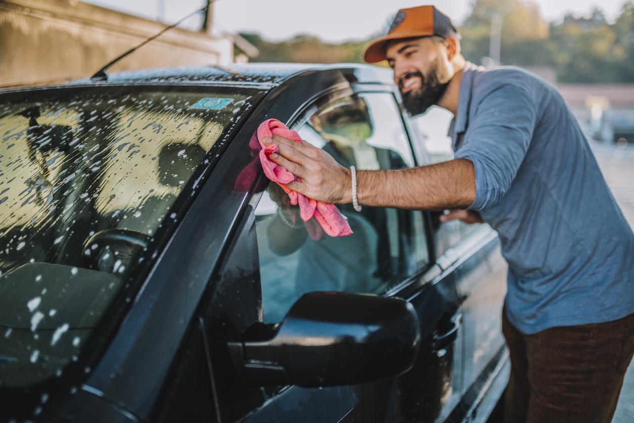 Handsome man washing car