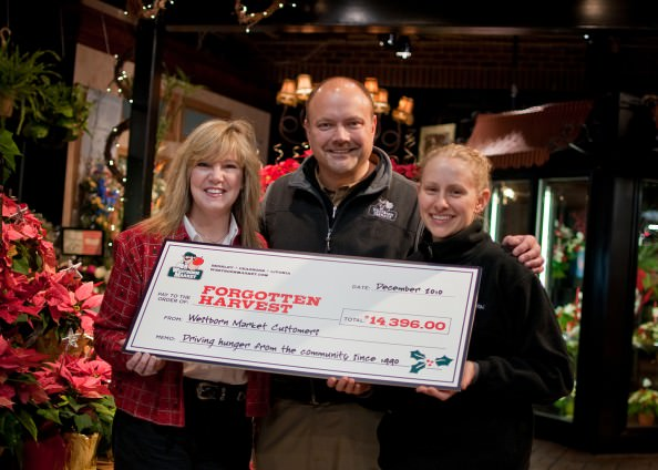 Forgotten Harvest's Associate Development Director Cindy Corey, at left, accepts a donation of $14,396 from Westborn Market, presented by Bryan Bandyk, marketing director and Patricia Labatte, Berkley cashier and top fundraiser, for the store's holiday campaign to help feed the hungry in metro Detroit.