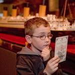 A young boy studies and authentic replica of a Titanic boarding pass at the Titanic exhibit.