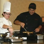 Chef Santaella and Chef Nicole Hassen prepare tostones in the Oakwood Common Dining Room for residents.