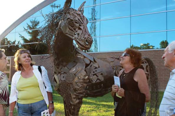 Community members look at horse sculpture called Gaze by James Oleson, Jr.