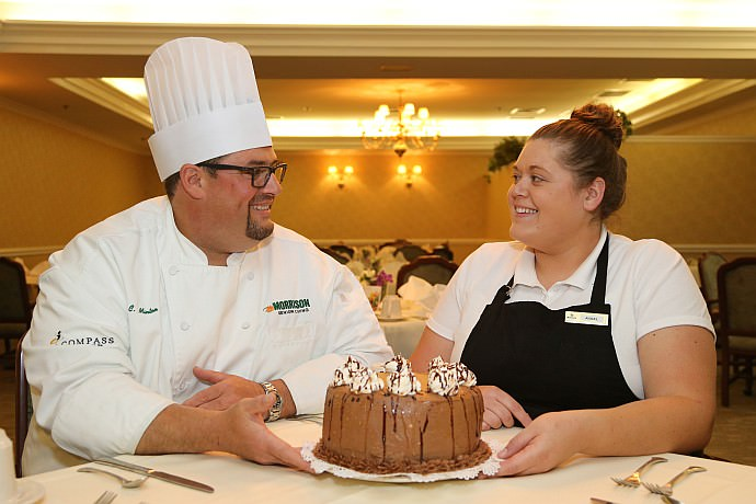 Baker Angel Hagen shows Chef Minton her creation of a chocolate, caramel-layered torte with sea salt.