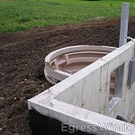 Window well installation shown on a new home's foundation.