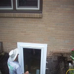 Window installation in progress, putting in a inswing basement window for easy egress.