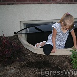 Egress window well for emergency exit. A little girl demonstrates an easy escape through the well.