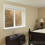 An egress window and well installed in a finished basement bedroom, ensuring a safe exit.