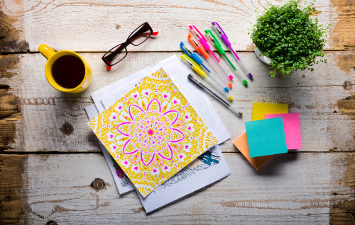 Adult coloring book page with colored pens